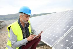 Mature-field engineer-on-building-roof-checking-solar-panels